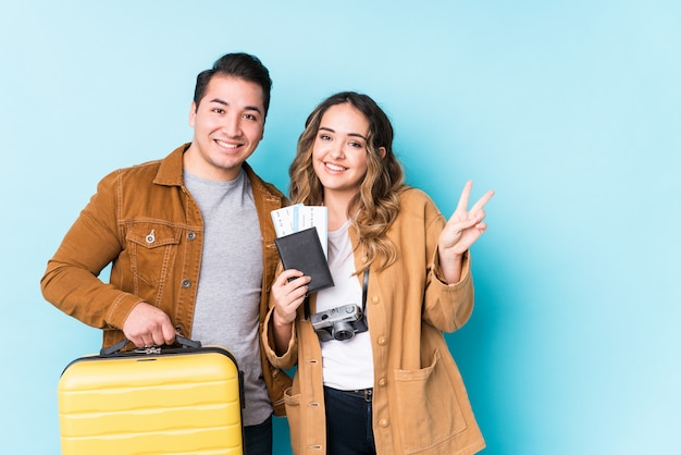Young couple ready for a travel isolated showing number two with fingers.