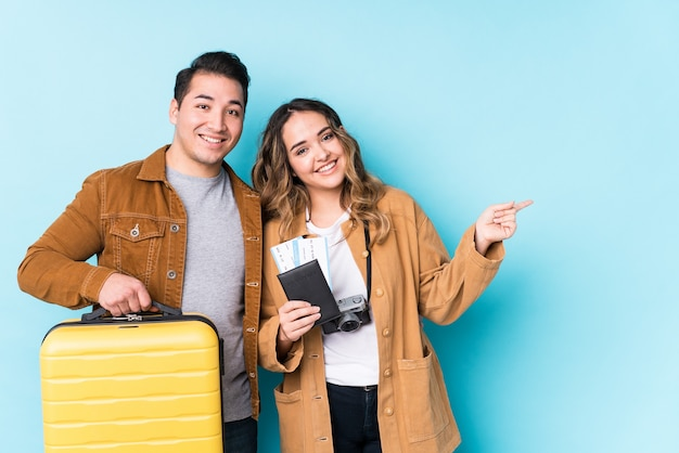Young couple ready for a travel isolated smiling and pointing aside, showing something at blank space.