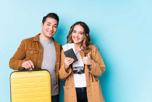 Young couple ready for a travel isolated smiling and raising thumb up