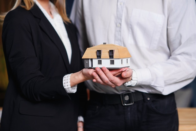 Young couple, realtor holding 3d model of house.