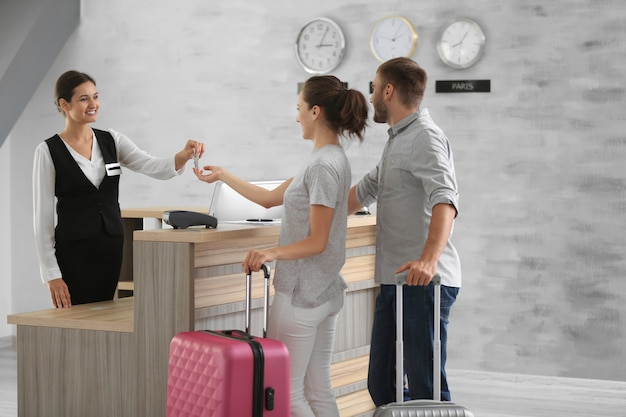 Молодая пара получает ключ от гостиничного номера на стойке регистрации