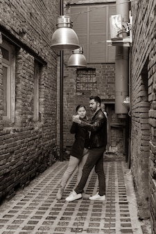 Young couple rehearsing a dance in the old alley, monochrome