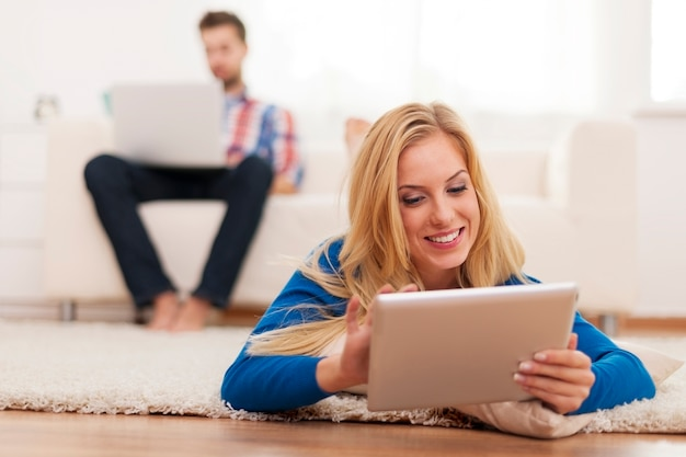 Молодая пара отдыхает дома с электронным оборудованием