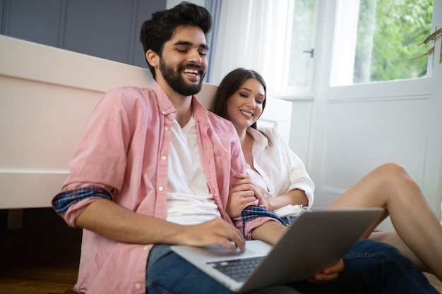 Young couple relaxing on bed with laptop. love, technology, happiness, people and fun concept.