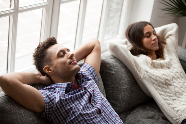 Young couple relaxing on comfortable sofa holding hands behind head