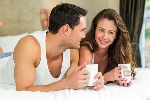Young couple relaxing and having cup of coffee on bed