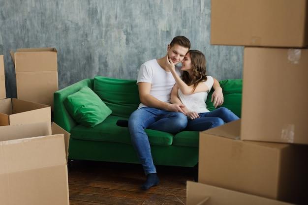 家の引っ越しからカートンを開梱した後、笑ってリラックスした若いカップル