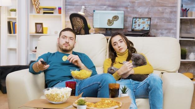 テレビを見ている猫と一緒にソファでリラックスする若いカップル。チップを食べる男。