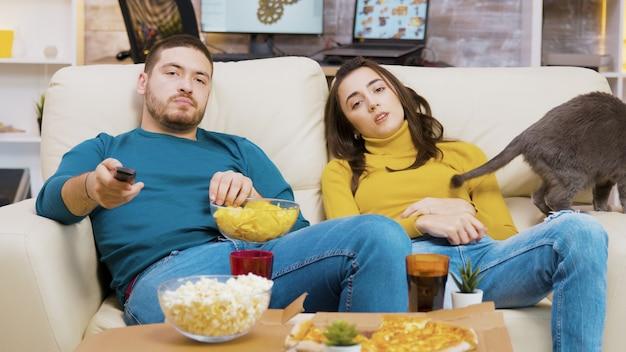 Молодая пара отдыхает на диване с их кошкой, смотря телевизор. человек ест чипсы.