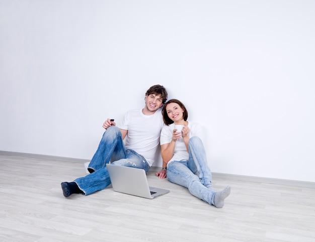 Coppia giovane rilassante seduta nella stanza vuota con il computer portatile e bere il tè