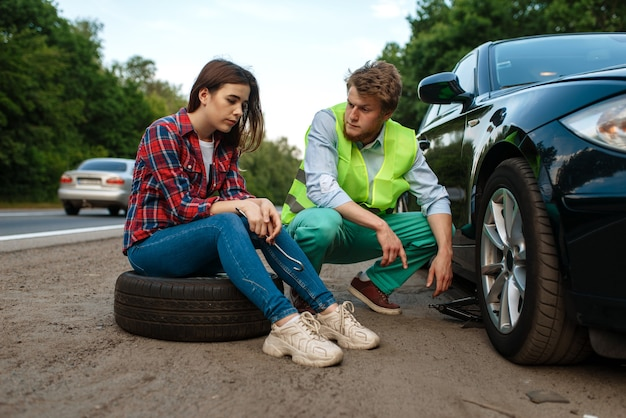 Young couple repair flat tyre, car breakdown. broken automobile or emergency accident with vehicle, trouble with punctured auto tire on highway