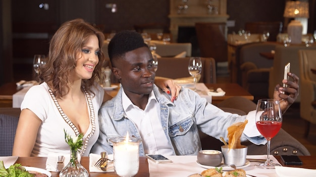 Young couple in restaurant using smartphone.