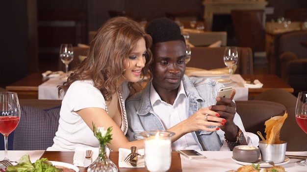 Young couple in restaurant using on smartphone.
