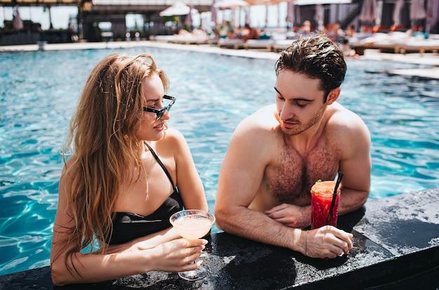 Молодая пара, отдыхая в бассейне