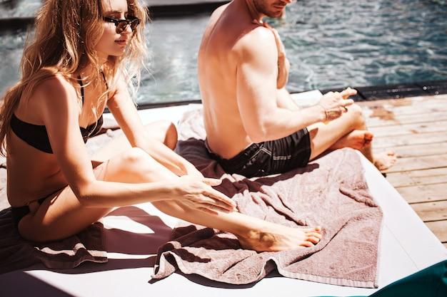スイミングプールで休んでいる若いカップル。日焼け止めクリームを足に塗っているスリムでしっかりした女性のカットビュー。男は横に座って、体に日焼け止めスプレーを使用しています。