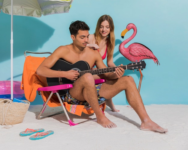 Young couple resting on beach in studio