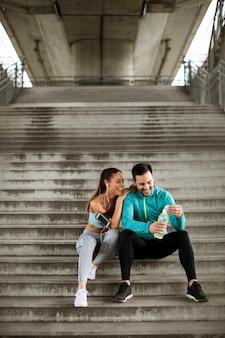 都市環境で水のボトルでトレーニング中に休んでいる若いカップル