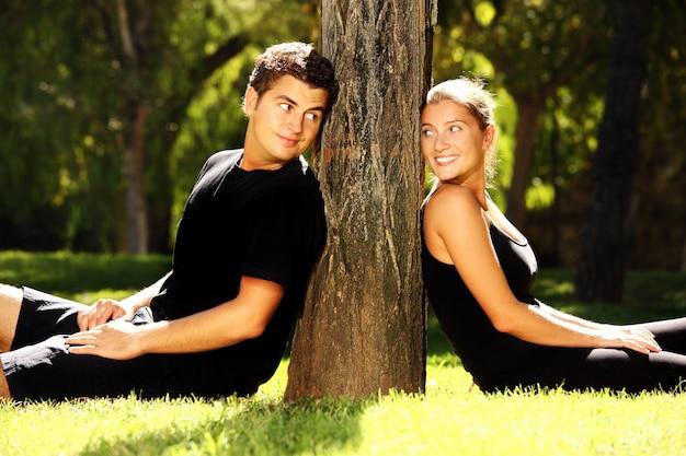 木の近くの公園で休んでいる若いカップル