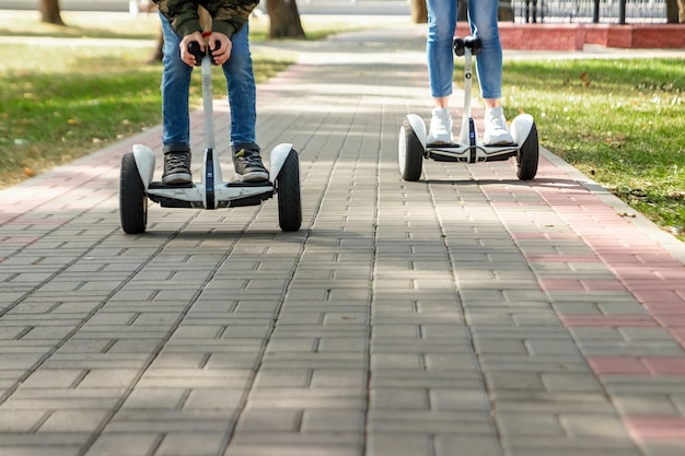 A young couple riding a hoverboard in a park
