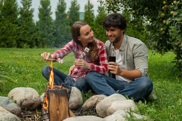 Молодая пара жарит зефир на пикнике у костра