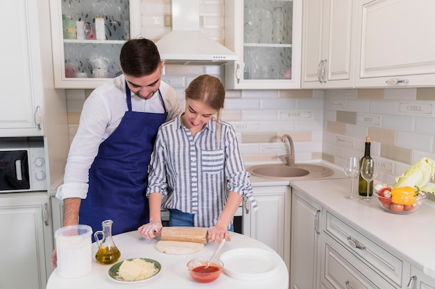Young couple rolling dough for pizza in kitchen