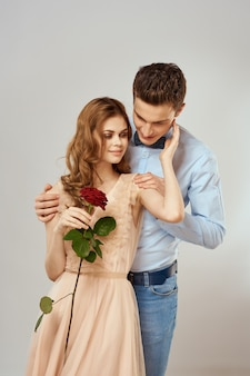 Young couple romance hug relationship dating red rose light studio background. high quality photo