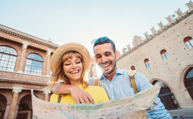 Young couple in rome. boyfriend and girlfriend holding city map visiting the beautiful italian city at holiday moment