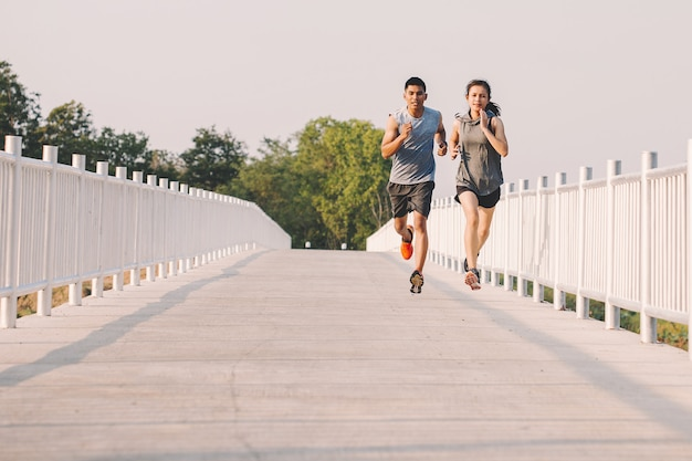 Young couple runner running on running road in city park
