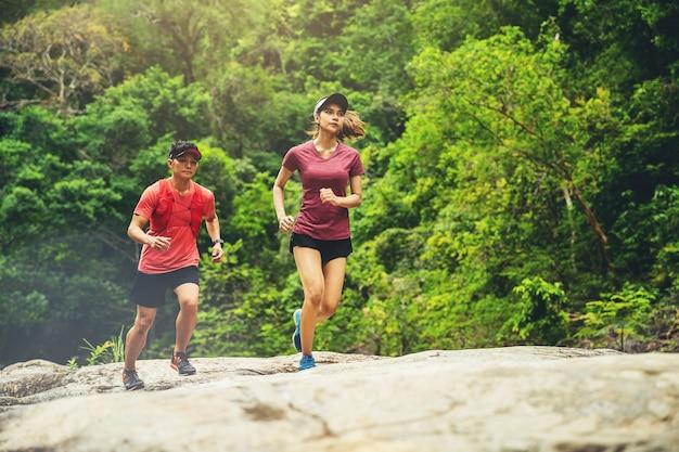 숲길에서 여름 동안 야생 숲으로 흔적을 달리는 젊은 부부 주자