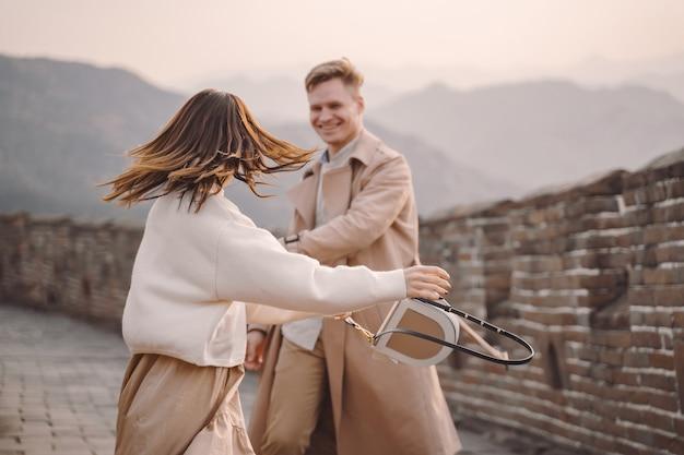 Молодая пара бегает и вертится у великой китайской стены