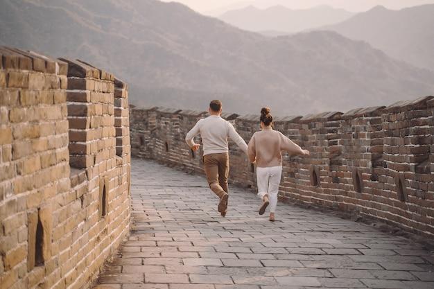 젊은 부부는 중국의 만리 장성에서 달리기와 달리기