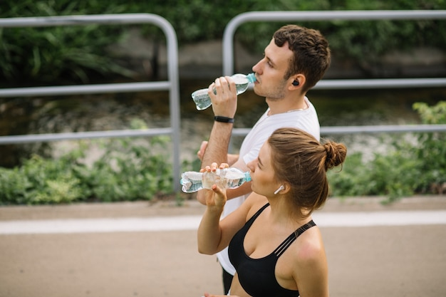 Young couple running in city park with plastic botle of water in hands, joint sports, cheerfulness, city sport healthy lifestyle, fitness together, summer evening, runners, drinking water, thirst