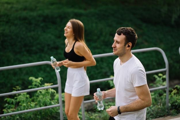 手に水のボトル、共同スポーツ、陽気、都市スポーツのライフスタイルと都市公園で走っている若いカップル
