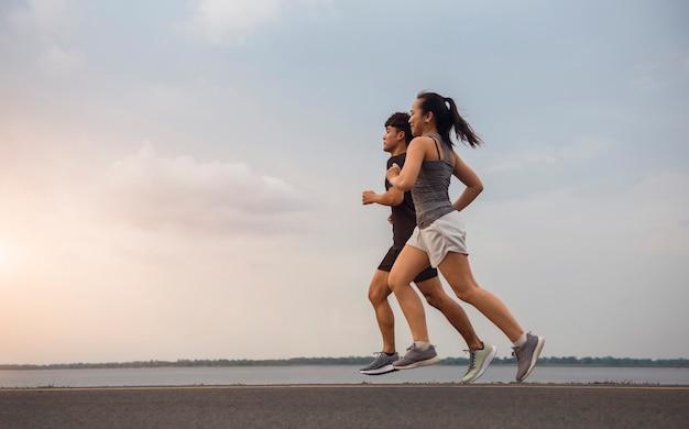 通りを走っている若いカップルが運動のために走っている