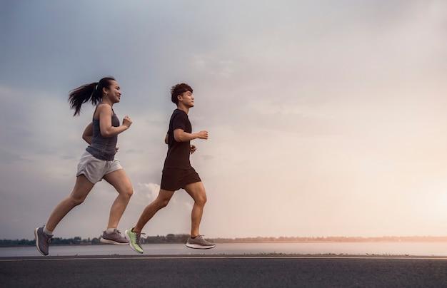 美しい光で運動のために通りを走っている若いカップル