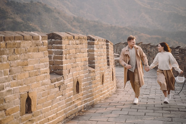 Young couple running and twirling at the great wall of china