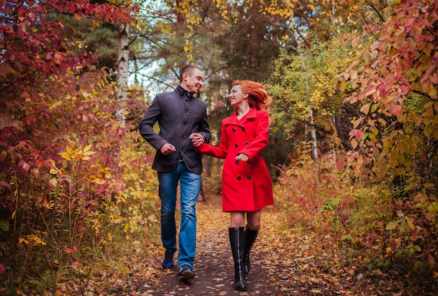 Young couple runs in autumn forest among colorful trees