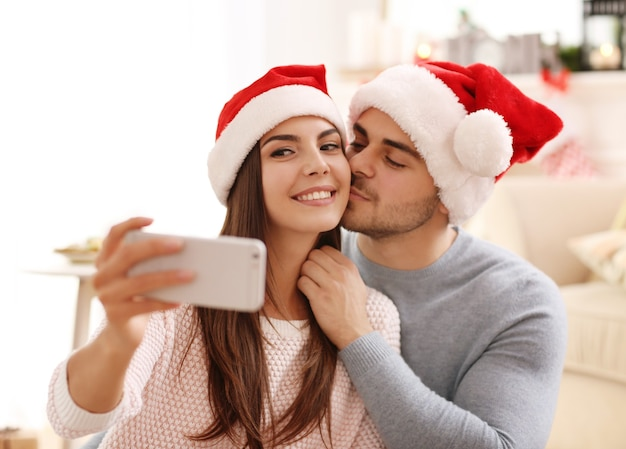 Young couple in santa claus hats making selfie indoors