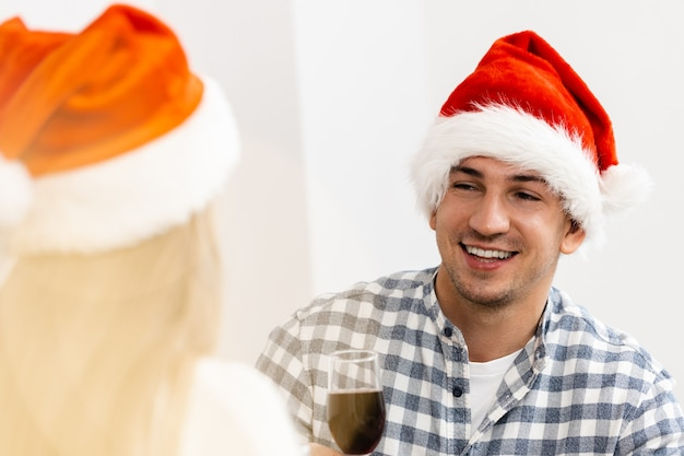 Young couple in santa hats drinking wine and celebrating christmas