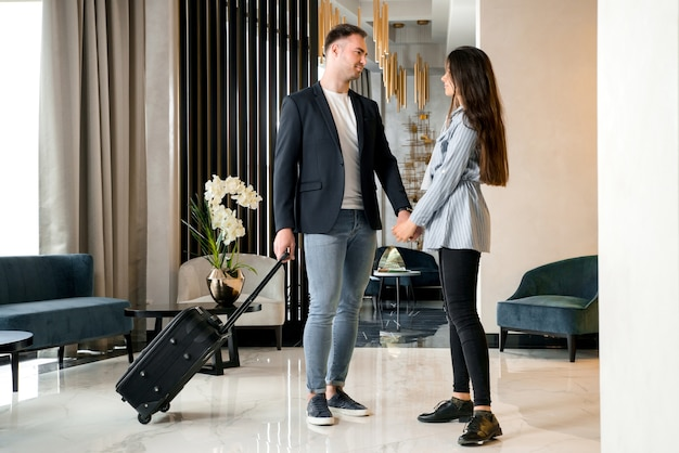 Young couple saying goodbye standing in hotel lobby before man leaving