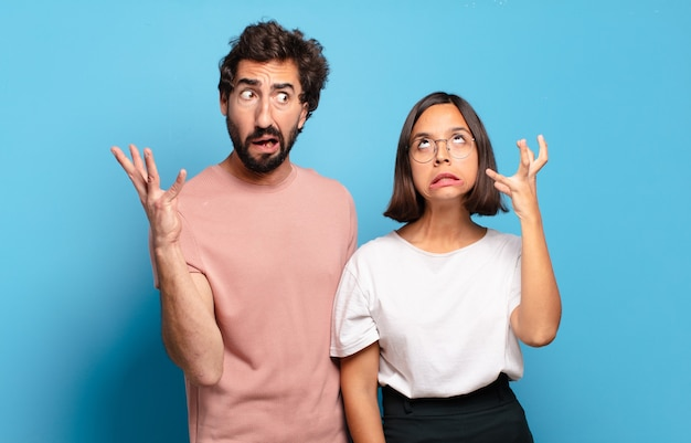 Young couple screaming with hands up in the air, feeling furious, frustrated, stressed and upset