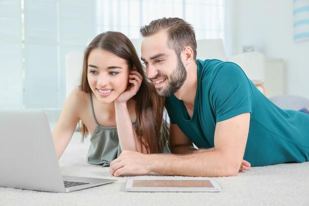 집에서 노트북을 사용 하여 정보를 검색하는 젊은 부부