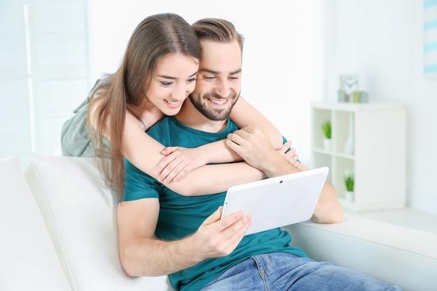 집에서 태블릿을 사용 하여 정보를 검색하는 젊은 부부