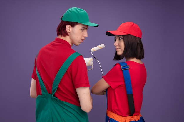Giovane coppia ragazzo serio ragazza sicura di sé in uniforme da operaio edile e berretto in piedi dietro la vista tenendo il rullo di vernice che si guarda l'un l'altro isolato sul muro viola