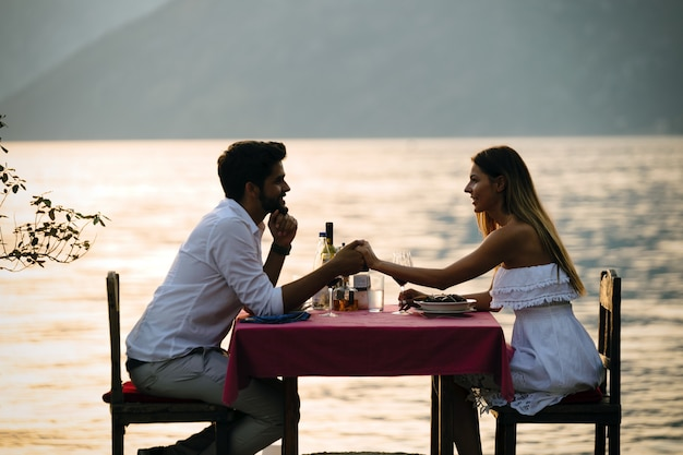 ビーチでロマンチックなサンセットディナーを共有する若いカップル