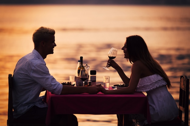 トロピカルリゾートでロマンチックなサンセットディナーを共有する若いカップル