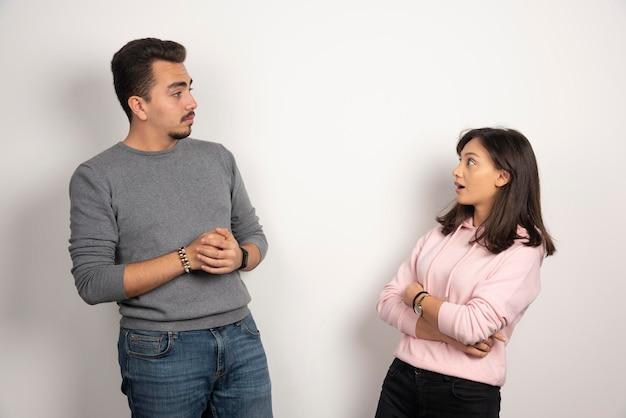 Giovani coppie che condividono le loro storie su bianco.