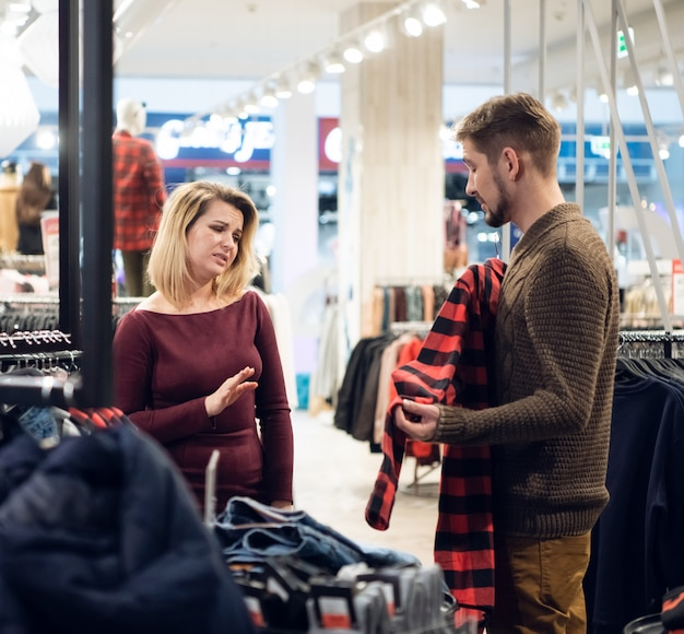 Young couple shopping for clothes in a male department, the girl does not like the shirt her boyfriend has picked