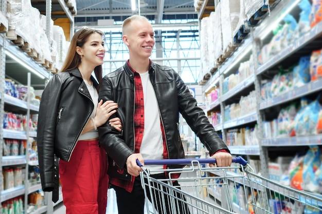 スーパーマーケットで買い物をする若いカップル。製品を見ている男と女