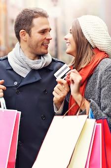 Молодая пара, делающая покупки в городе с помощью кредитной карты
